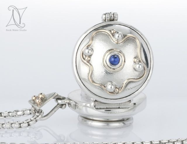 sapphire silver working compass locket with lid open showing gold waves and droplets around the sapphire